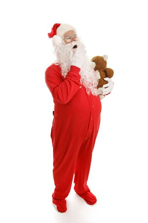 Santa Clause yawning and ready for bed in his footy pajamas with his teddy bear.  Full body on white.