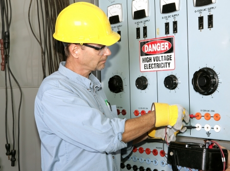 Actual electrician working on an industrial power distribution center. All work shown is being performed according to industry code and safety standards.