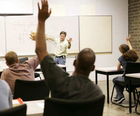 Photo for Adult education class raising hands to ask questions.  - Royalty Free Image