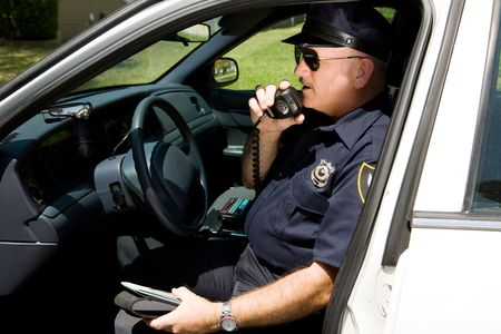 Photo for Police officer in squad car, radioing in to headquarters.   - Royalty Free Image
