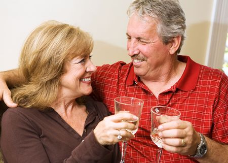 Beautiful mature couple enjoying a glass of wine and gazing into each others eyes.  の写真素材