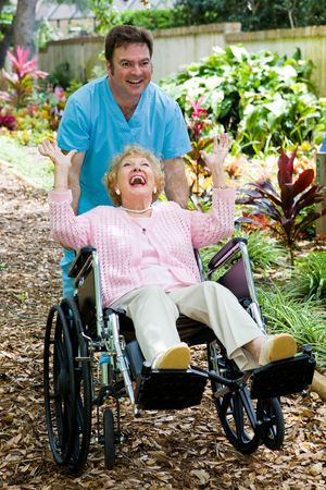 Friendly orderly and senior lady having great fun as he pushes her wheelchair.