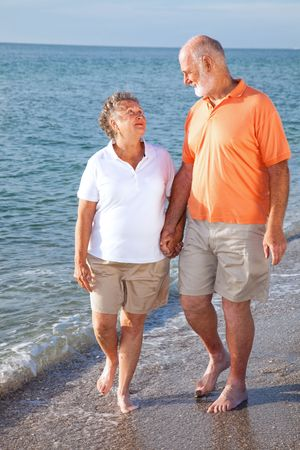 Vacationing senior couple takes a romantic stroll on the beach.
