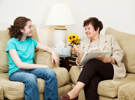 Teen girl being interviewed by a mature woman.  Could be college or job interview, or counseling session.
