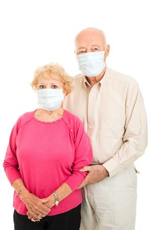 Worried senior couple wearing surgical masks to protect against flu epidemic.  Isolated.