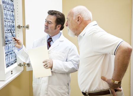 Doctor explains a CT scan of the spine to his senior patient.