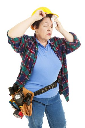 Tired female construction worker wipes sweat from her forehead.