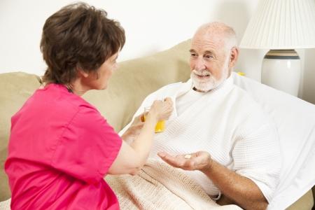 Home health nurse giving an elderly patient juice to make his medicine go down.