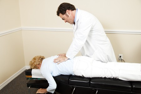 Chiropractor adjusting a senior woman's back.  Room for text