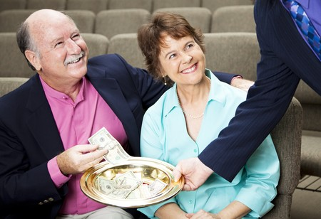 Couple placing money in a church collection plate.