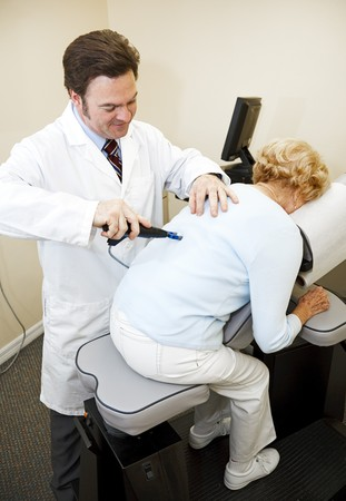 Chiropractor using an eletrical tool and computer to diagnose and adjust a patient's spine alignment.