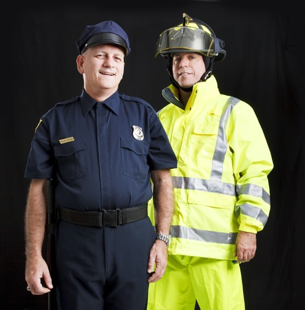 Photo for Police officer and firefighter photographed together over a black background.   - Royalty Free Image