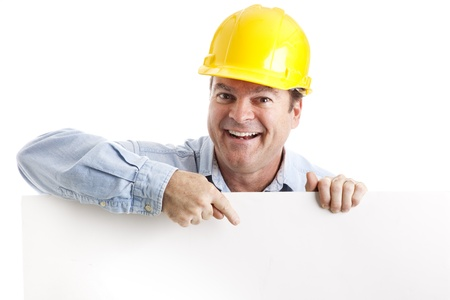 Construction worker leaning over and pointing to blank white space.  Isolated.