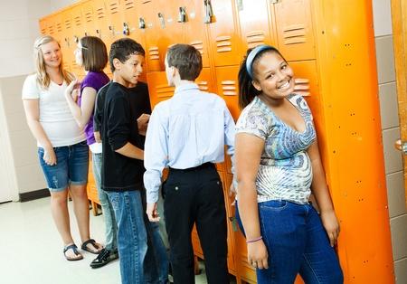 Teenagers in the hallway, at their lockers between classes.