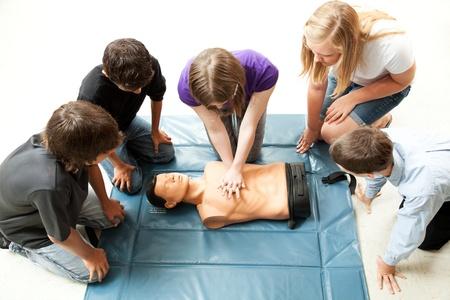 Photo pour Teenage students use a mannequin to practice life saving techniques. - image libre de droit