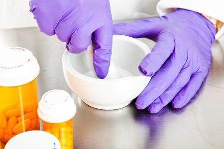 Photo pour Closeup view of a pharmacist's hands, using a mortar and pestle.   - image libre de droit