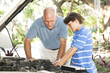 Father teaching his son how to service and repair the car.
