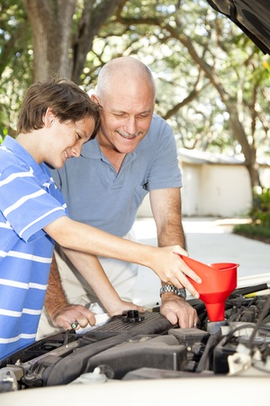 Father and son changing the oil on the family car.