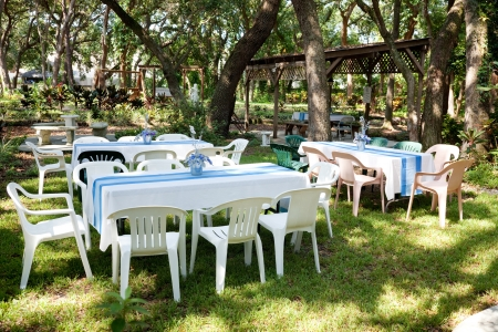 Tables and chairs set up for a garden party, wedding, or other outdoor event.