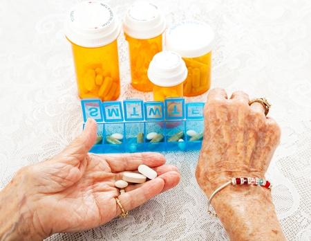Photo pour Closeup view of an eighty year old senior woman's hands as she sorts her prescription medicine.   - image libre de droit