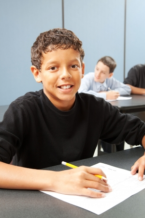 Photo pour Handsome ethnic boy in school class.  Real person in real classroom.   - image libre de droit