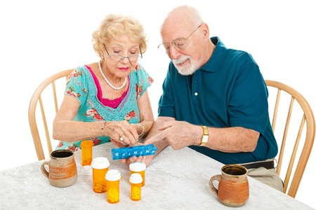Photo pour Senior couple at the table, sorting their medications for the week.  White background. - image libre de droit