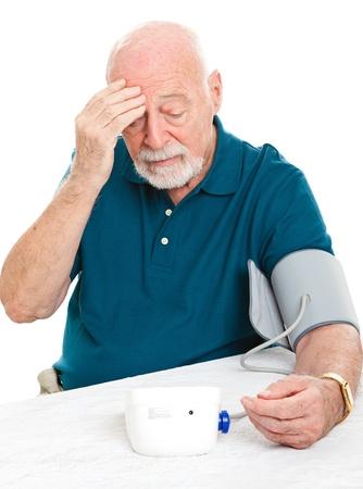 Worried senior man monitors his blood pressure at home.