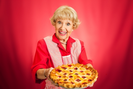 Sweet retro grandmother holding a freshly baked lattice top cherry pie   Red background with plenty of room for text