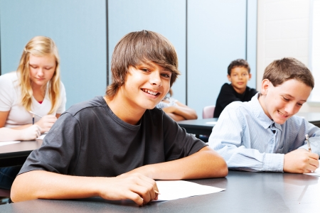 Photo pour Class of teenagers in school, focus on suntanned boy in the front.   - image libre de droit