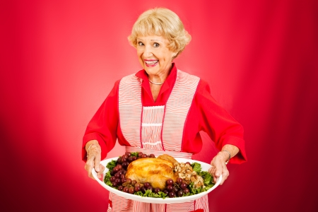 Photo pour Sweet grandmother holding a beautifully cooked turkey dinner.   - image libre de droit