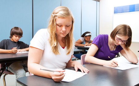 Photo pour Pretty blond girl taking a test with her high school class.   - image libre de droit