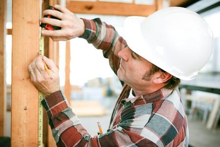 Carpenter taking measurements on a construction site.