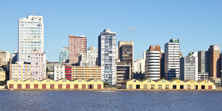 Porto Alegre port warehouse. Downtown buildings and blue sky are shown too.