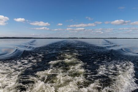 Boat waves, Clouds and reflections in Lough Corrib lake, Cong, Mayo, Irelnd