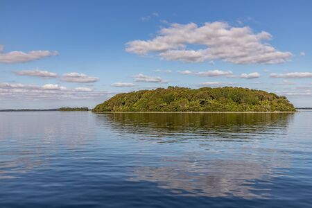 Island, Clouds and reflections in Lough Corrib lake, Cong, Mayo, Ireland