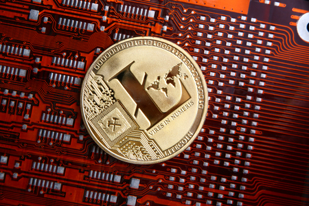 Litecoin gold coin on a orange or red & black computer flexible circuit.