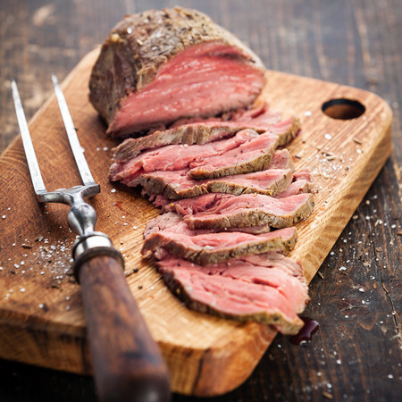 Roast beef on cutting board and meat fork