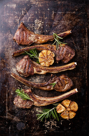 Roasted lamb ribs with spices and garlic on dark steel background