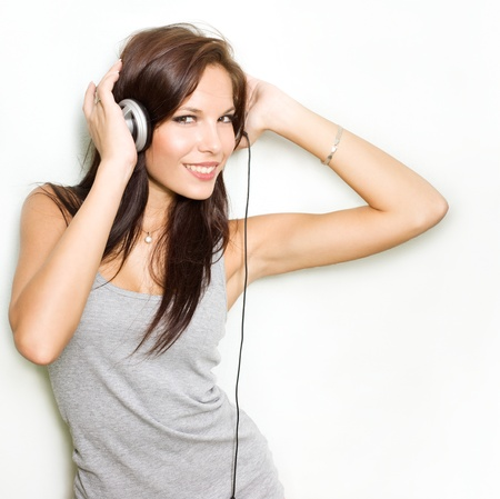 Hot dymanic young brunette listening to music in headhones.