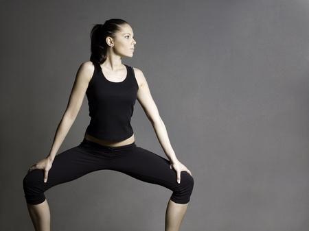 Foto de Beautiful slim young fitness brunette girl in squat position. - Imagen libre de derechos