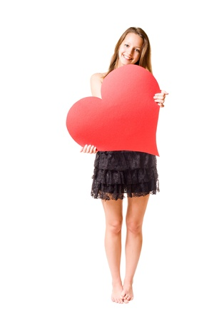 Gorgeous young brunette fooling around with large red heart shape, isolated on white background.の写真素材