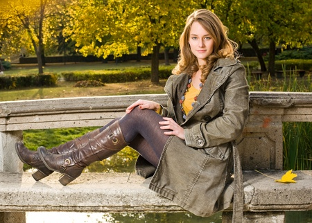Full figure portrait of beautiful young woman in the park at fall.