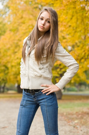 Beautiful young model dressed for chilly weather posing outdoors in the park.