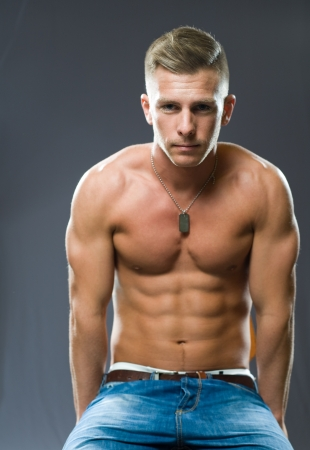 Portrait of a very fit, ripped young man flexing muscles.
