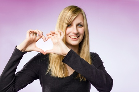 Portrait of a blond beauty on pink background showing heart sign.