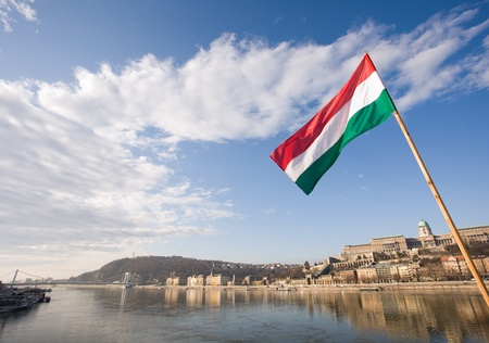 The Hungarian flag over river Danube and facades of historic buildings in Buda.