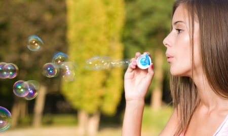 Dreamy blond teen beauty blowing soap bubbles.