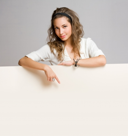 Portrait of a beautiful young brunette woman with blank billboard sheet