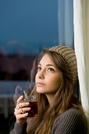 Portrait of a pensive young brunette woman with hot tea.の写真素材
