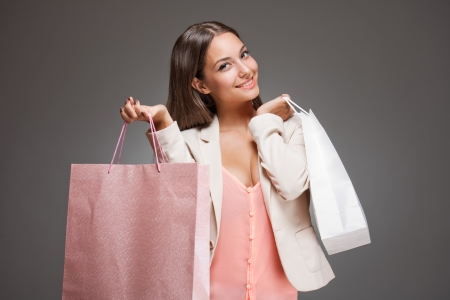 Portrait of a brunette beauty with pink and white shopping bags.